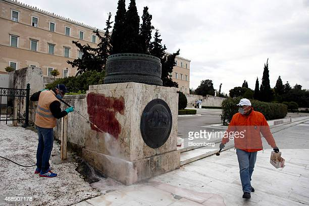 Municipal workers clean graffiti from a wall outside the Greek parliament building in Athens Greece on Wednesday April 8 2015 Russian President...