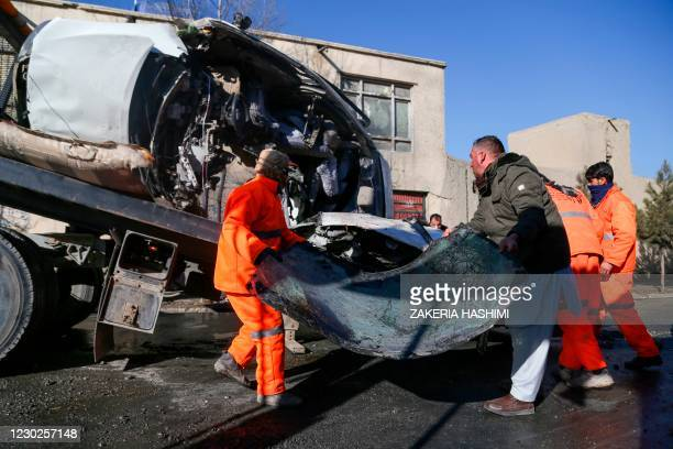 Municipal workers clean up debris at the site of a bomb attack in Kabul on December 22, 2020. - Two women doctors working at an Afghan prison with...