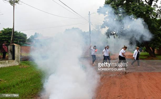 Municipal workers cross a street during an Aedes aegypti --the mosquito that can spread dengue fever-- fumigation in San Lorenzo, Paraguay on January...