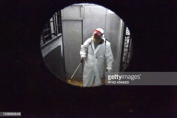 Municipal workers dressed in protective gear disinfect a building during the COVID19 coronavirus pandemic in the Bab elOued district of Algeria's...