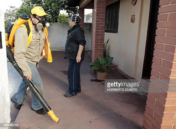 Municipal workers fumigate a house in Asuncion during an operation to eradicate the Aedes aegypti mosquito vector of the dengue fever on May 25 2013...