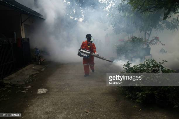 Municipal workers fumigates an areas of housing complex against Aedes Aegypti mosquitos as a measures to control a dengue outbreak amids Covid-19...