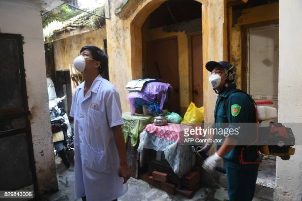 Municipal workers prepare to spray chemicals to kill mosquitos at a residential home in downtown Hanoi on August 11 2017 as authorities make efforts...