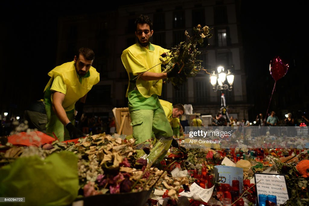 Municipal workers remove flowers and candles from a tribute in memory of the victims of last´s week attack at the Ramblas boulevard in Barcelona, on August 28, 2017. The number of people killed in twin vehicle attacks in Spain last week rose to 16, local authorities in Barcelona said. The attacks on Las Ramblas boulevard in Barcelona and in the seaside resort of Cambrils left around 120 wounded. / AFP PHOTO / Josep LAGO
