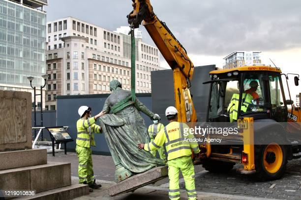 Municipal workers remove the statue of slaveowner and slave merchant Robert Milligan after a petition in West India Quay district of London United...