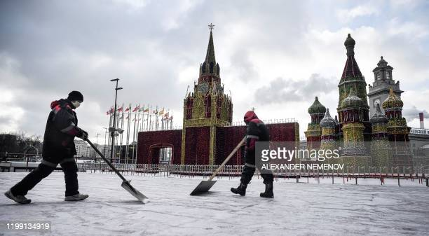 Municipal workers wearing medical face masks clean the snow in front of a model of Saint Basil cathedral in Moscow on February 7 2020 Russian...
