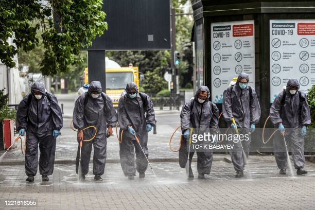 Municipal workers wearing protective suits, amid concerns over the spread of the COVID-19 coronavirus, desinfect a deserted street in Baku on June...
