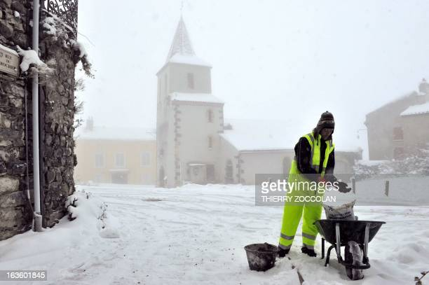 Municipality employee spreads salt on the road covered by the snow on January 31, 2012 in Vodable, centre France, due to the first snow falls of the...