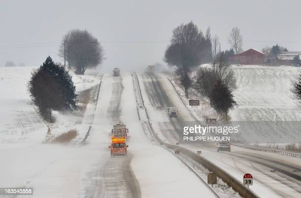 Municipality employees salt the snowy A25 highway on March 12 2013 in Godewaersvelde northern France during a heavy snow storm on France Overnight...