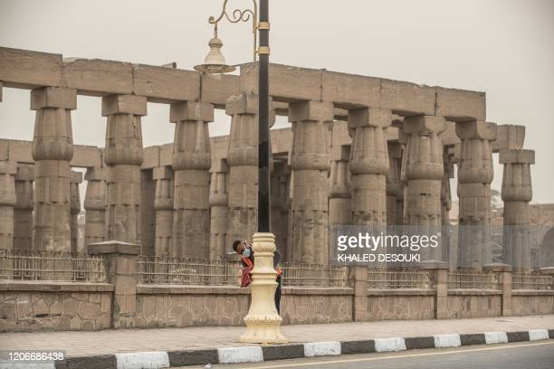 Municipality worker cleans lamp posts amid a sandstorm and coronavirus fears outside the Luxor Temple in Egypt's southern city of Luxor on March 12,...