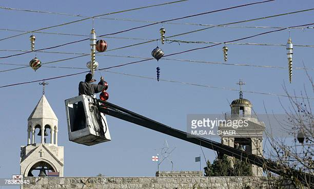 A municipality worker decorates Manger Square outside the Church of the Nativity in the Palestinian West Bank town of Bethlehem 11 December 2007...