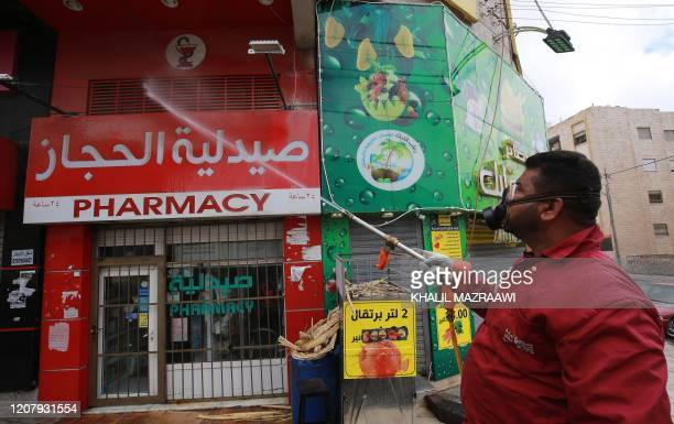 A municipality worker disinfects a pharmacy in the Jordanian capital Amman as part of preventive measures against the spread of the coronavirus...