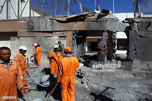 Municipality workers clean up the debris as Libyan security forces inspect the scene of a car bombing outside the United Arab Emirates embassy...