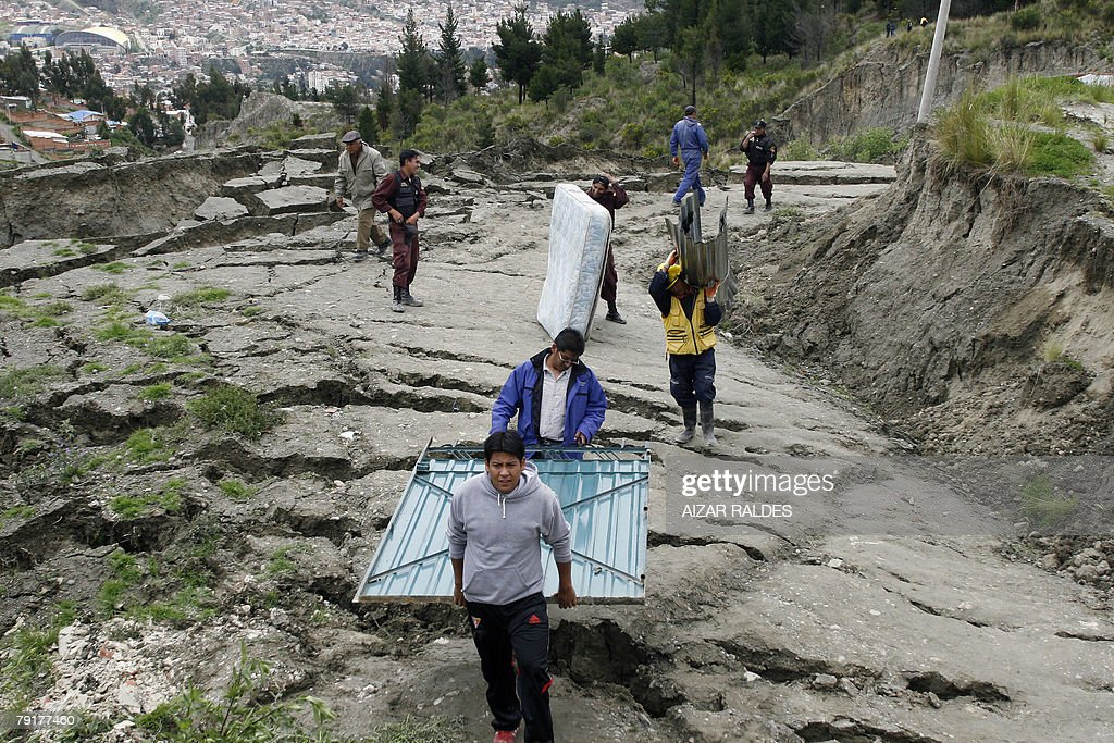 Municipality workers help residents to carry some of their belongings 23 January, 2008 in Alpacoma valley in La Paz, after heavy rains caused a landslide that devastated 11 houses. The Bolivian government decreed on Tuesday a national emergency to counteract damages caused by heavy rains and floods battering the country since last November. According to official sources, 22 people died so far and about 20,000 families have been damaged.