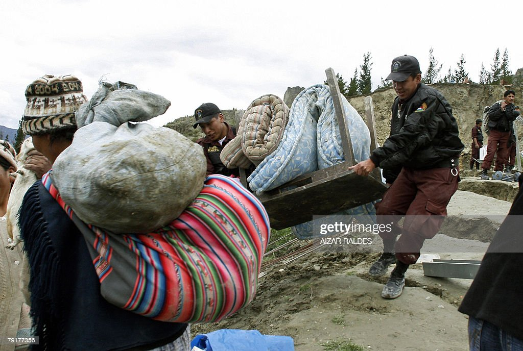 Municipality workers help residents to recover part of their belongings from the rubble 23 January, 2008 in Alpacoma valley in La Paz, after heavy rains caused a landslide that devastated 11 houses. The Bolivian government decreed on Tuesday a national emergency to counteract damages caused by heavy rains and floods battering the country since last November. According to official sources, 22 people died so far and about 20,000 families have been damaged.