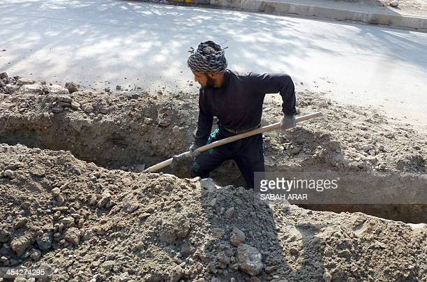 A municiple worker digs a trench along the side of a main road following heavy flooding in different districts of the capital Baghdad on December 8...