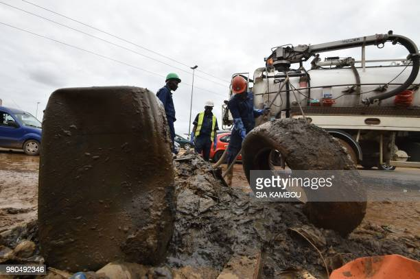 Municiple workers clear the street drains of debris and mud following flooding in the coastal city of Abidjan on June 21 2018 Ivory Coast's...