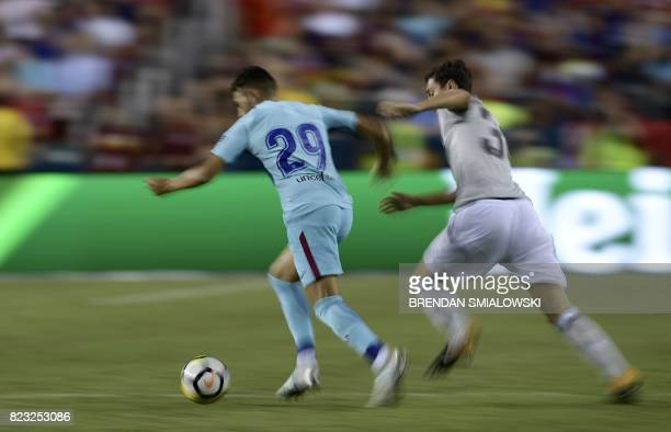 Munir El Haddadi of Barcelona and Demetri Mitchell of Manchester United fight for the ball during their International Champions Cup football match on...