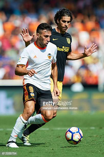 Munir El Haddadi of Valencia competes for the ball with Tiago Cardoso of Atletico de Madrid during the La Liga match between Valencia CF and Atletico...