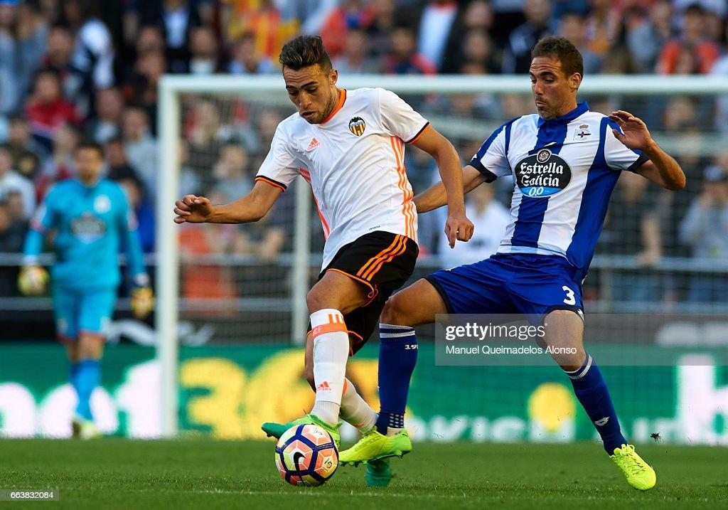Munir El Haddadi (L) of Valencia is tackled by Fernando Navarro of Deportivo de La Coruna during the La Liga match between Valencia CF and Deportivo de La Coruna at Mestalla Stadium on April 2, 2017 in Valencia, Spain.