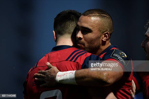 Munster Rugby's fullback Simon Zebo is congratulated by teamates after scoring a try during the European Champions Cup rugby union match between...