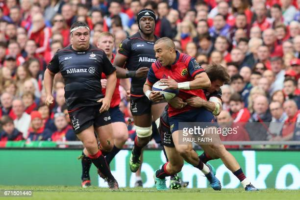 Munster's Irish fullback Simon Zebo is tackled by Saracens' New Zealand born Scottish wing Sean Maitland during the rugby union Champions Cup...