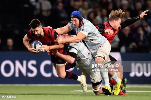 Munster's Irish scrum half Conor Murray is tackled by Racing's Irish lock Donnacha Ryan and flanker French Wenceslas Lauret during the European...