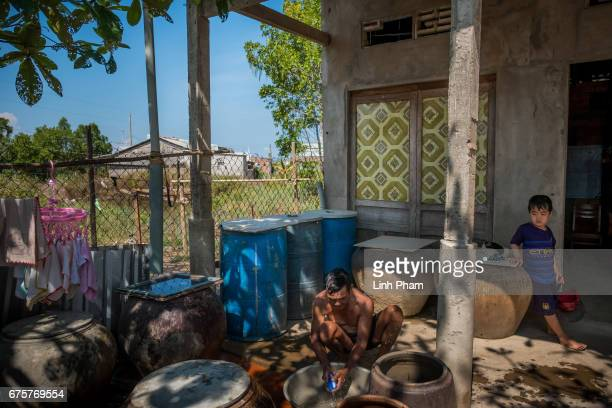 Muoi 'Cua' 61 A farmer takes a shower with fresh water bying from the water truck on April 28 2017 in Thua Duc Village Binh Dai District Ben Tre...