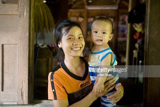 Muong ethnic minority woman Bui Thi Ngoan with her baby in their house in Mat hamlet Tien Phong commune Da Bac district Hoa Binh province Poor...