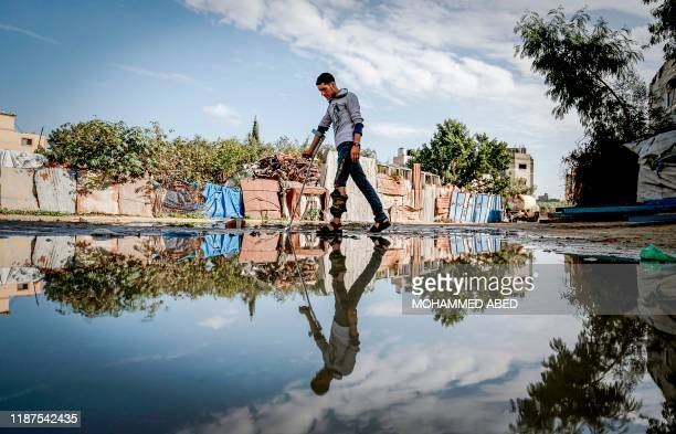TOPSHOT Murad alWadyah a Palestinian youth who was previously injured in a prior demonstration walks with a crutch past a rainwater pool near his...