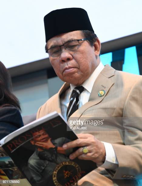 Murad Ebrahim chairman of Moro Islamic Liberation Front reads a magazine with an image of Philippine President Rodrigo Duterte on the cover during a...