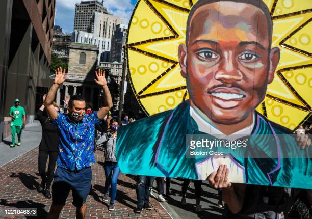 Mural artist David Fichter holds his painting of Ahmaud Arbery while participating in a protest and march organized by Beyond New Perspectives...