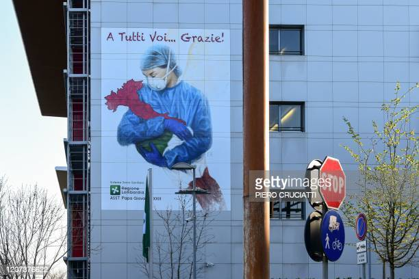 A mural by artist Franco Rivolli Art depicting a nurse wearing a face mask with wings behind her back and cradling Italy is pictured on a wall of the...