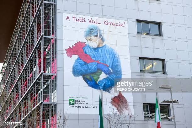 Mural by artist Franco Rivolli Art, depicting a nurse wearing a face mask, with wings behind her back and cradling Italy, is pictured on a wall of...