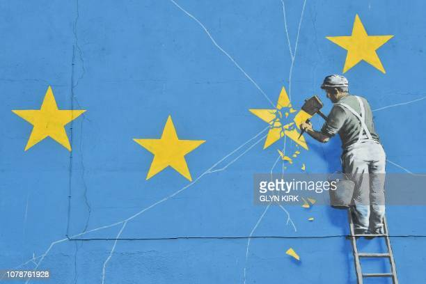 Mural by British artist Banksy, depicting a workman chipping away at one of the stars on a European Union themed flag, is pictured in Dover, south...