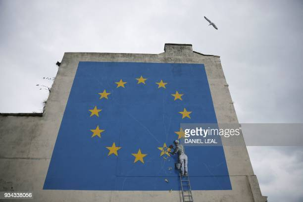 TOPSHOT A mural by British artist Banksy depicting a workman chipping away at one of the stars on a European Union themed flag is pictured in Dover...