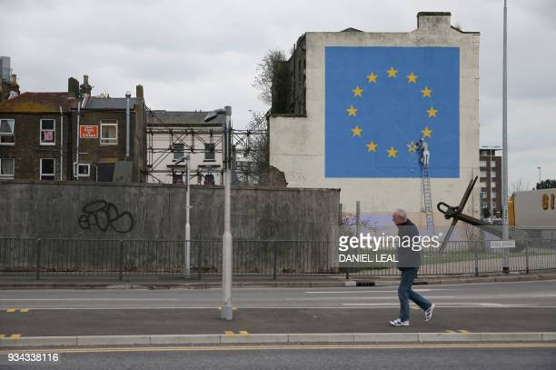 A mural by British artist Banksy depicting a workman chipping away at one of the stars on a European Union themed flag is pictured in Dover south...