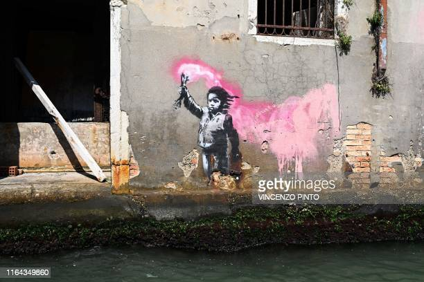 Mural by British street artist Banksy, of a child holding a pink flare, is pictured on August 27, 2019 on a building in Venice. / RESTRICTED TO...