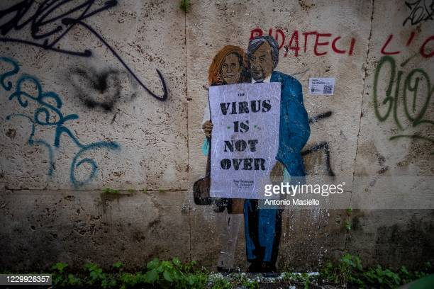 "Mural by street artist TVBOY depicts the two Italian virologists Roberto Burioni and Ilaria Capua with a banner reading ""Virus is not over"", on a..."