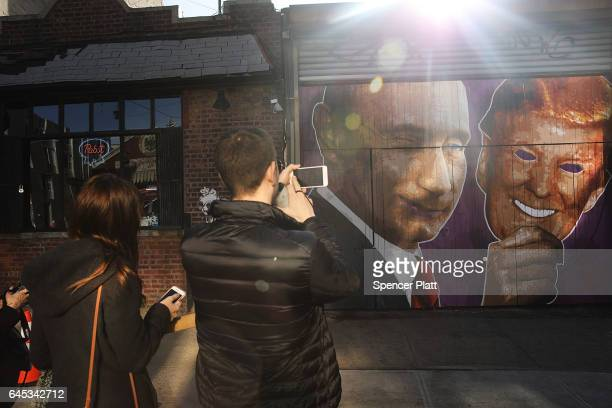 A mural depicting a winking Vladimir Putin taking off his Donald Trump mask is painted on a storefront outside of the Levee bar in Brooklyn on...