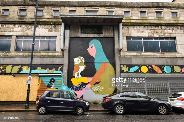 A mural depicting a woman holding an owl by Matt Sewell adorns a disused building in Belfast Northern Ireland on Wednesday April 4 2018 Brexit...