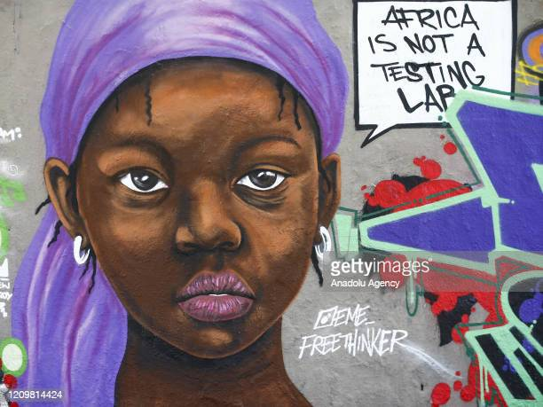 A mural depicting 'black woman' with a message reading Africa is not a testing laboratory to refer a quotation of two doctors in France is seen amid...