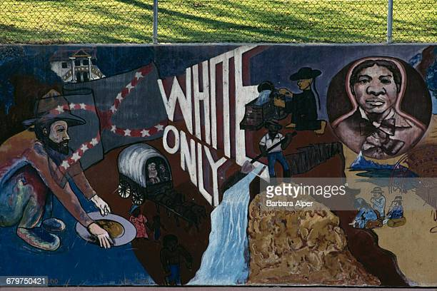 A mural depicting scenes from American history the Gold Rush and the words 'White Only' Los Angeles California USA January 1990