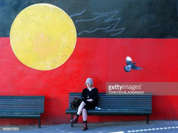 A mural of the Aboriginal flag featuring the rising sun and the ochre earth adorns a wall in Sydney 07 April as Australia prepares for a race...