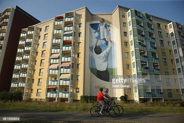 A mural on the side of communistera apartment blocks shows a father tossing his daughter into the air on July 7 2015 in Hoyerswerda Germany...