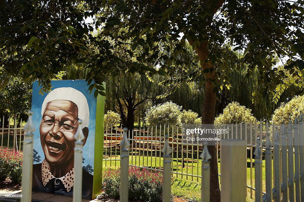 A mural portrait of former South African President Nelson Mandela is surrouned by a fence in Thokoza Park April 8, 2013 in Johannesburg, South Africa. Thokoza Park is situated right next to Regina Mundi Catholic Church, a site of resistance during apartheid and place of shelter during the 1976 Soweto Uprising. Former South African President Nelson Mandela returned to his Johannesburg home Saturday after spending nine days in the hospital with pneumonia.