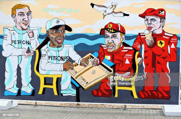 A mural showing Lewis Hamilton of Great Britain and Mercedes GP and Sebastian Vettel of Germany and Ferrari playing backgammon as Valtteri Bottas of...