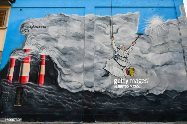 TOPSHOT A mural showing Pope Francis by artist Mauro Pallotta known as MauPal is pictured on September 21 2019 in Albano Laziale southeast of Rome...