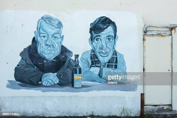Mural showing the actors Jean Gabin and JeanPaul Belmondo from the 1962 French film Un singe en hiver at Villerville Calvados Normandy France