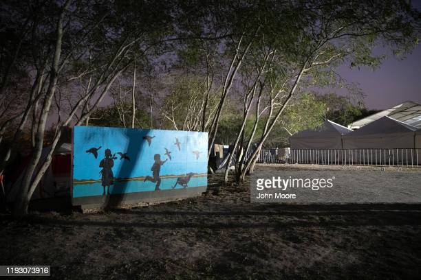 A mural stands near shelters known as macro tents recently constructed by the Mexican government which remain virtually unused at a camp for asylum...